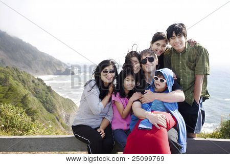 Multiracial Family Of Seven Sitting By The Pacific Ocean. Little Boy Is Disabled With Cerebral Palsy
