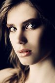 Close-up portrait of a beautiful young woman with natural makeup. Gray background. Beauty, cosmetics poster