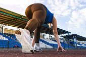 Beautiful Athlete On A Race Track Is Ready To Run. Runner In Black Leggings And A Blue Shirt Is At T poster