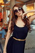 Close-up Portrait Of Young Elegant Brunette In Black Dress And Sunglasses, Touching Her Face. Fashio poster