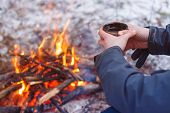Traveler Hands Holding Mug From Thermos Near The Bonfire. Drinking Tea From Mug At Camp poster