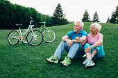 Happy Senior Couple Sits On The Grass, Enjoying The Rest After Riding Bicycles. Bicycles Stand Near  poster