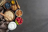 Nutrition Healthy Eating Ingredients On Black Concrete Background. Oats, Berries, Nuts, Almon Milk A poster