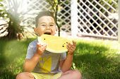Happy Child Eating Yellow Watermelon In The Garden. Boy Sitting With Fruit Outdoors On Grass In Priv poster