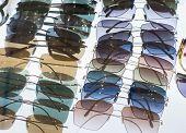 Various Different Sunglasses On Display Shelf In Sunglasses Shop. Sunglasses On Sale poster