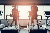 Bearded Man And Young Woman On Treadmills In Gym. Man With Athletic Body. Healthy Lifestyle And Spor poster