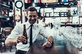 Young Happy Man Drinking Beer In Modern Bar. Sitting In Pub. Bottle Of Beer. Young Man With Beer. Ma poster