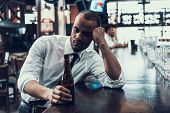 Sad Young Man With Bottle Of Beer Sitting In Bar. Drunken Guy In Modern Pub. Unhealthy Lifestyle. Ad poster