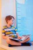 Parents And Kids Sitting Near Window And Having Fun At Kitchen. A Boy With A Book Sits On A Window S poster