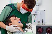 picture of uv-light  - Dentist using UV light on patients teeth - JPG