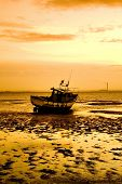 stock photo of beach hut  - silhouetted fishing boat waiting for the tide to come in in the golden sunset on the essex coast