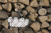 foto of chicken-wire  - Fresh white eggs placed in a wire basket hanging from a woodpile - JPG