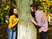 Couple In Love Plays Behind Tree In Autumn Park. Man And Woman With Happy Faces On Autumn Trees Back poster