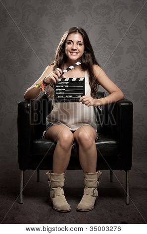 young woman holding a movie clapper board