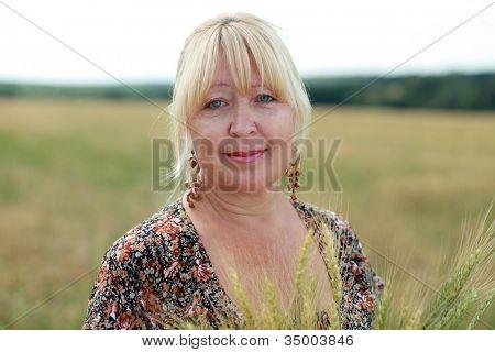 portrait of an elderly woman in a wheat field