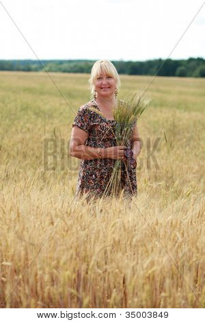 portrait of an elderly woman in a wheat field
