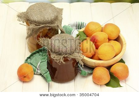 canned apricots and jam in a jars and ripe apricots in bowl on white wooden table