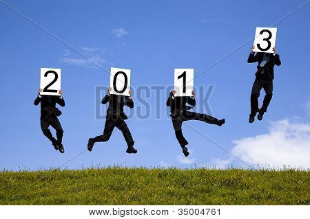 businessman holding 2013 and jumping on the green field