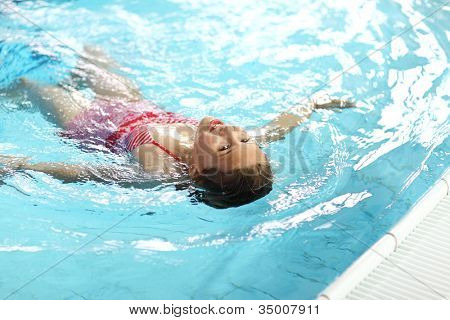 Child swimming backstroke in the pool