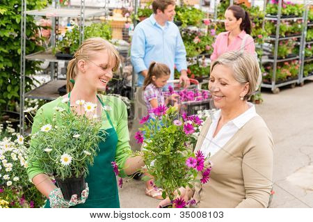 Female florist give advice to senior customer shopping for flowers
