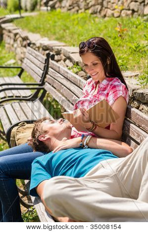 Young happy couple relax on park bench sunny day