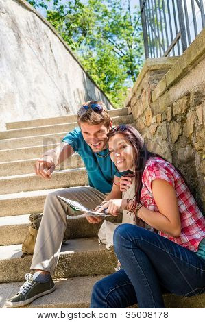 Young couple on holiday with city map point direction smiling