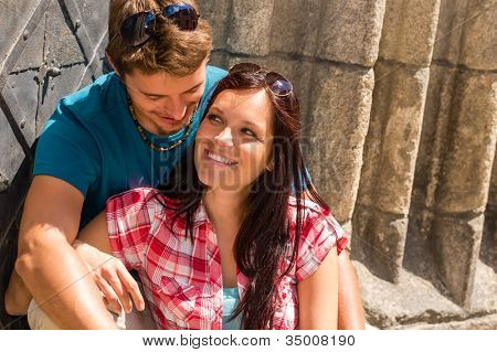 Young couple sitting on building steps smiling enjoy love moment