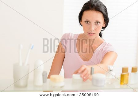Young woman take beauty care product from bathroom shelf