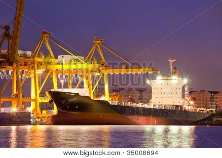 Container Cargo freight Industrial ship with working crane bridge unloading and loading goods in Bangkok shipyard Terminal at dusk for Logistic Import Export background