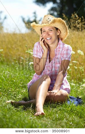 Happy attractive female talks over mobile phone, summer outdoor shoot