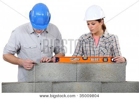 Bricklayers with a spirit level and plumb line