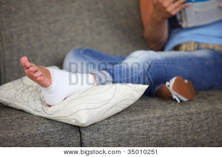 Woman with sprained ankle reading on the sofa