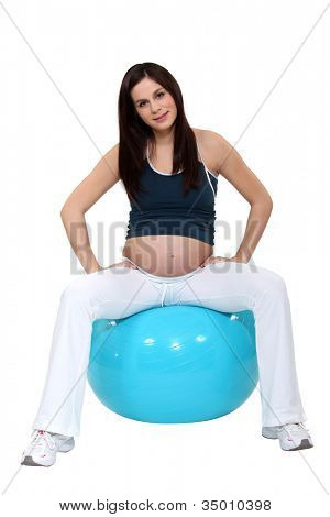 pregnant young woman sitting on inflatable balloon