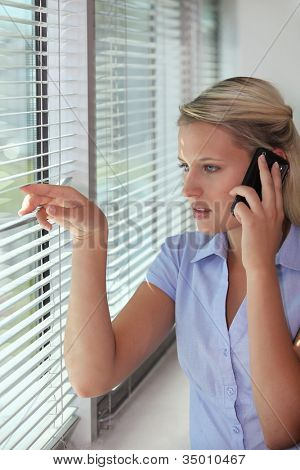 Woman on the phone looking through venetian blinds
