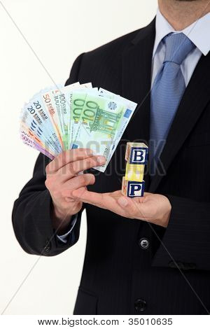 Businessman holding cash and the letters BTP