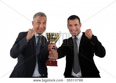 cheerful businessmen holding a golden cup