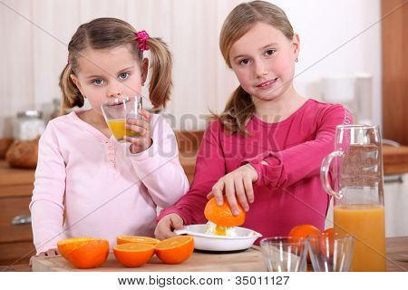 Girls squeezing oranges