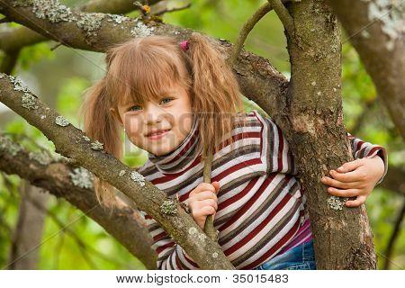 schönes kleines Mädchen posiert auf einem Baum im Garten sitzen.