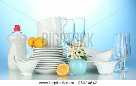 empty clean plates, glasses and cups with dishwashing liquid and lemon on blue background
