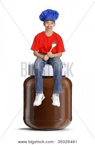 Little chef kid sitting over a chocolate pot,Little kid holding a chocolate spoon,child eating chocolate cream.