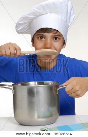 Little kid cooking on a metallic pan holding a spoon,little chef kid cooking,cooking children.