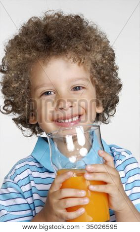 Happy little kid holding an orange juice glass,little kid drinking orange juice.