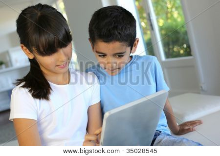 Children playing with electronic tablet at home