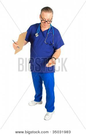full body image of Male nurse or doctor with chart and stethoscope around neck,  holding a handful of pills, isolated on white