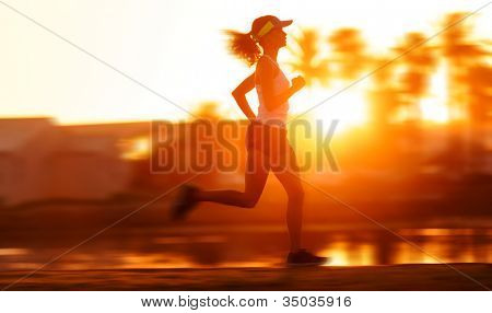 silhouette with motion blur of a woman athlete running at sunset or sunrise. fitness training of marathon runner.