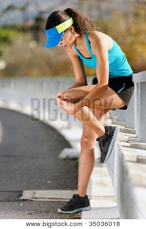 knee injury for athlete runner. woman in pain after hurting her leg while training for fitness marathon