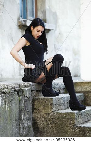 punk girl dressed in black, sitting on the stairs