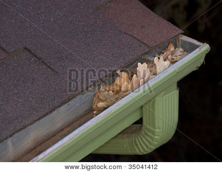 roof corner with gutter blocked by dry leaves - house maintenance problem