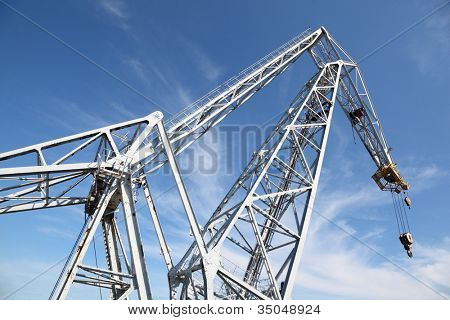 big white hoisting crane with hook at background of blue sky