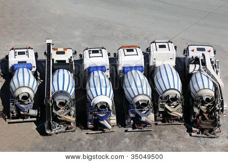 Six concrete mixer machines stand on asphalt at sunny day; back view